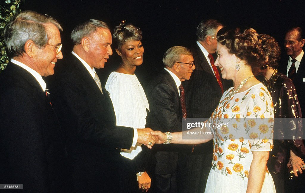 Queen Elizabeth ll shakes hands with singer Frank Sinatra watched by Perry Como and Dionne Warwick at a dinner at the studios of 20th Century Fox in Los Angeles on the 27th of February 1983.