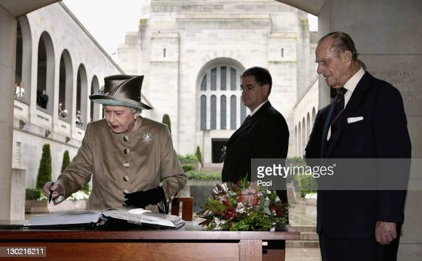 Queen Elizabeth ll signs the visitors book before departing the Australian War Memorial on October 25 2011 in Canberra Australia The Queen and Duke...