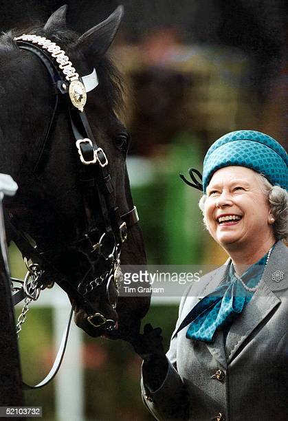 Queen Elizabeth Ll Smiling As She Reviews Troops Mounted On Horses At The Royal Windsor Horse Show.