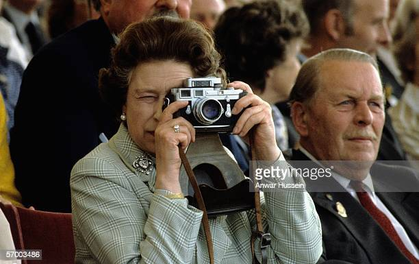 Queen Elizabeth ll takes photographs with her Leica camera at the Royal Winsdor Horse Show on May 16 1982 in Windsor England