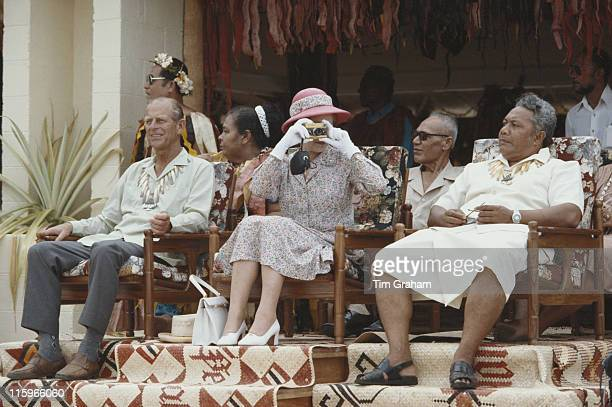 Queen Elizabeth ll taking a photograph with her gold Rollei camera sitting alongside Prince Philip during their tour of the South Pacific in Tuvalu...