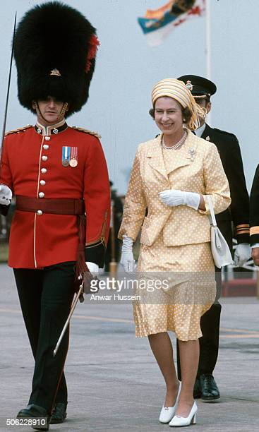 Queen Elizabeth ll walks beside a British soldier wearing a busby during a tour of Canada on July 16, 1976 in Canada.