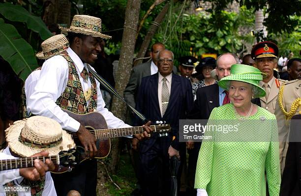 Queen Elizabeth Ll Watching A Group Of Musicians Whilst Attending The Governor General's Garden Fair At The Half Moon Hotel To See Jamaican Produce...