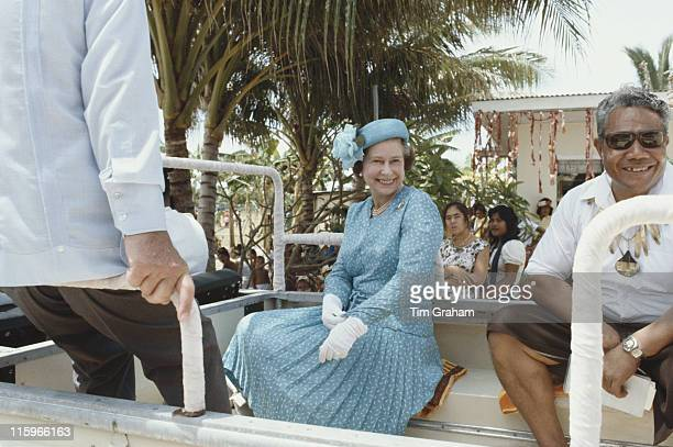 Queen Elizabeth ll wearing a blue dress and hat with white gloves during her tour of the South Pacific in Tavalu 27 October 1982