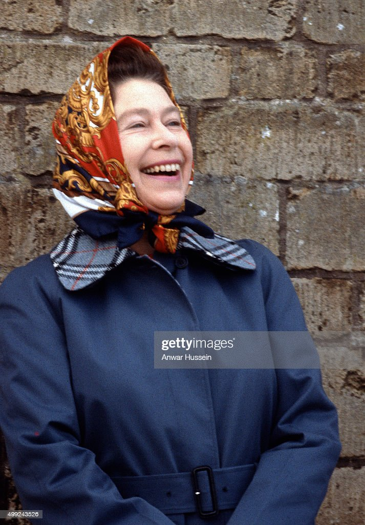 Queen Elizabeth ll, wearing a headscarf laughs during Badminton Horse Trials on April 01, 1979 in Badminton, England.