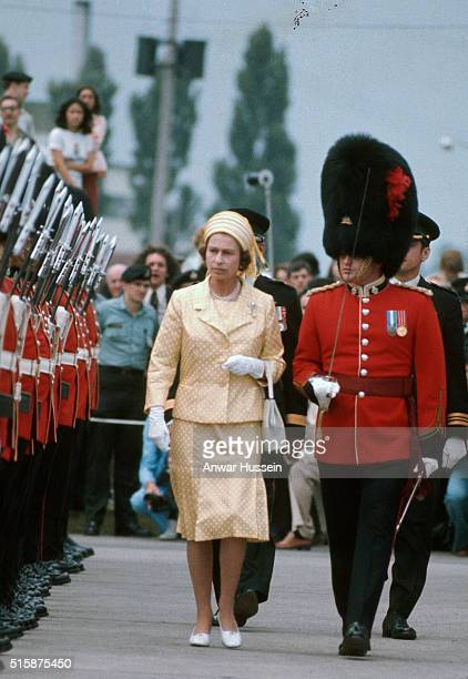 Queen Elizabeth ll wearing a yellow honeycomb style hat inspects a guard of honour of British soldiers during a tour of Canada on July 16 1976 in...