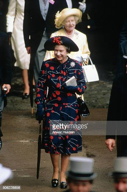 Queen Elizabeth ll wears red cherries on her hat and dress as she attends Royal Ascot on June 01, circa 190s in Ascot, England.