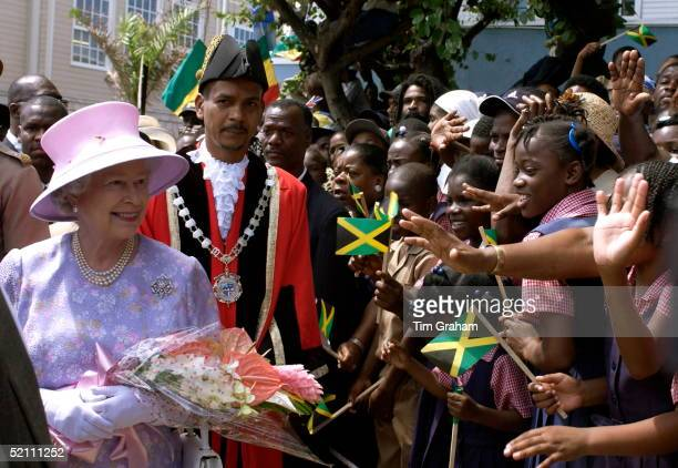 Queen Elizabeth Ll With The Mayor Of Montego Bay Smiling As She Meets An Enthusiastic Crowd Who Are Stretching Out Their Hands To Greet Her In Sam...