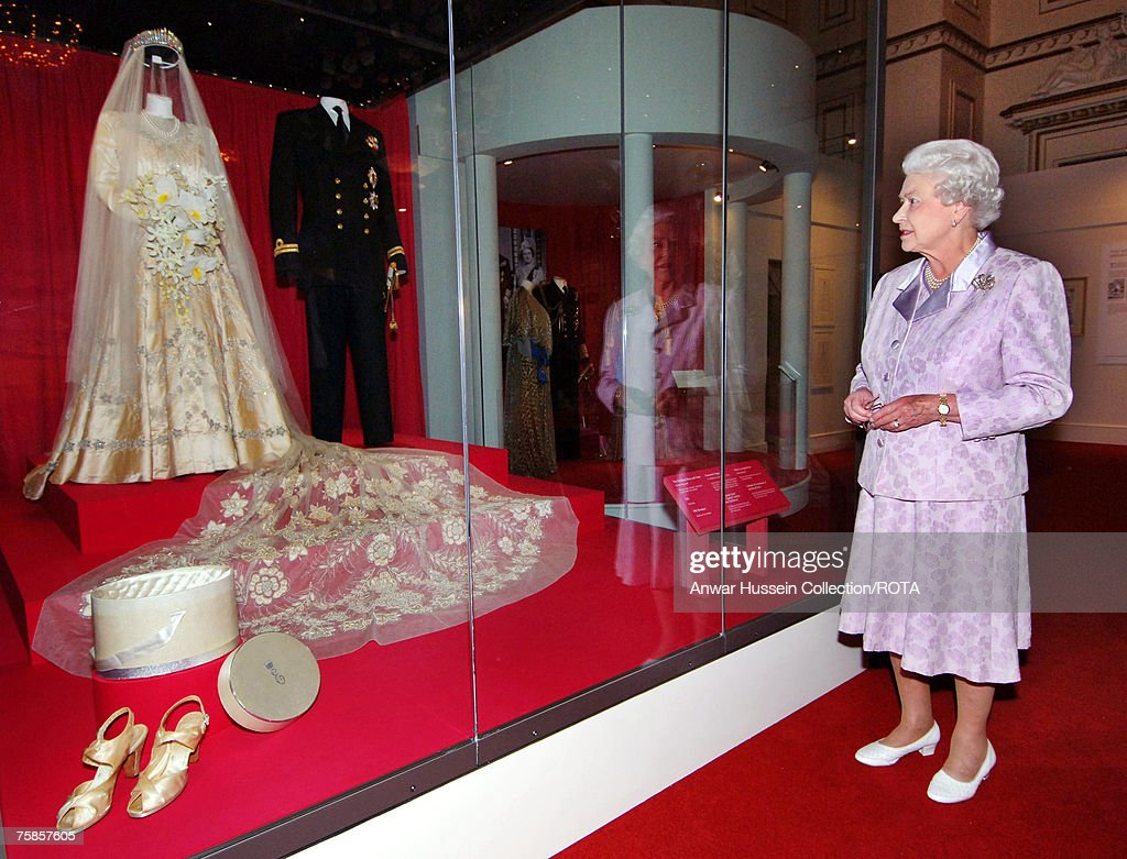 Queen Elizabeth looks at her 1947 wedding gown and 13 foot bridal trail designed by Norman Hartnell with the naval uniform worn by Prince Philip, Duke of Edinburgh which are on show for the Summer Opening Exhibition at Buckingham Palace to mark her Diamond Wedding Anniversary on July 24, 2007 in London, England.