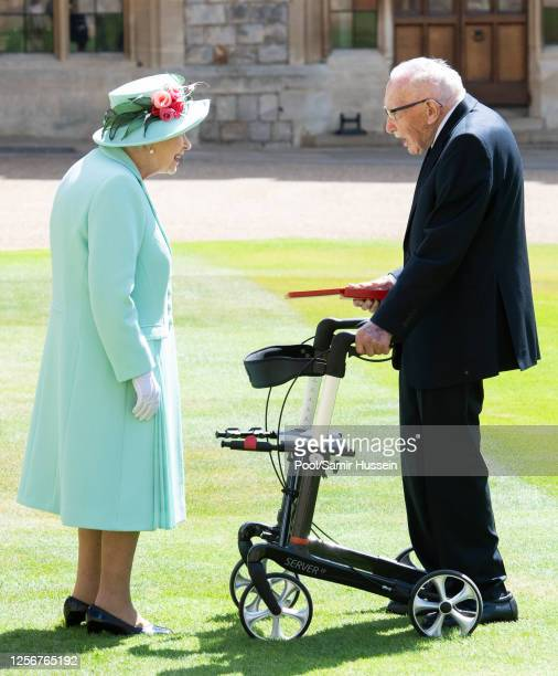 Queen Elizabeth presents the insignia of Knight Bachelor to Captain Sir Thomas Moore during an investiture ceremony at Windsor Castle on July 17 2020...