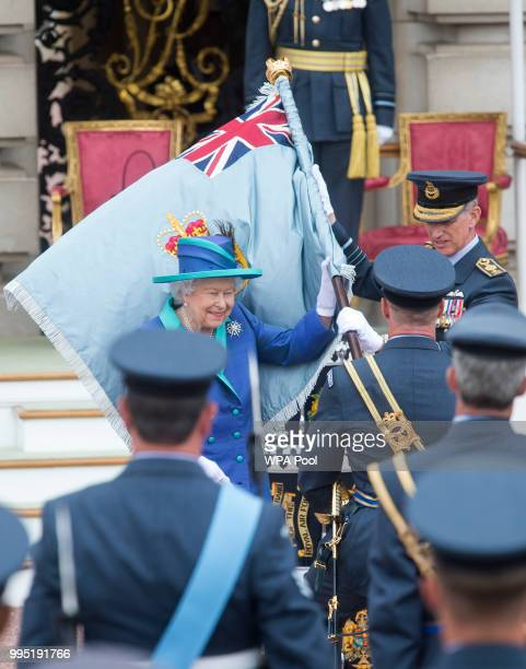 Queen Elizabeth presents The RAF with new Queen's Colours of their centenary during the RAF 100 ceremony at Buckingham Palace as members of the Royal...
