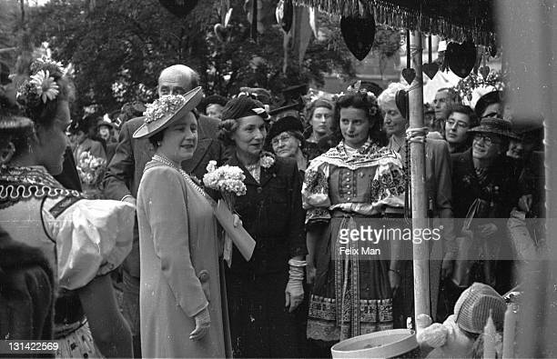 Queen Elizabeth Queen Consort to King George VI talking to stall holders at the Czechoslovakian stall of the Allied Nations' Summer Fair held in the...