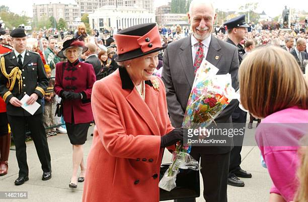 Queen Elizabeth receives flowers from a Canadian crowd before a luncheon October 6 2002 in British Columbia Canada The visit is part of a twelveday...