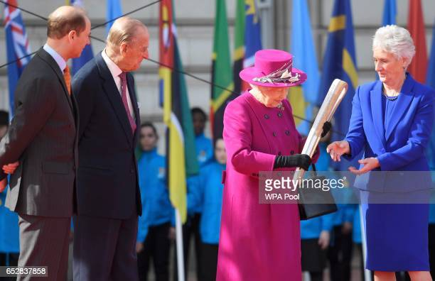Queen Elizabeth receives the baton from Louise Martin of the Commonwealth Games organizing committee during the launch of The Queen's Baton Relay for...