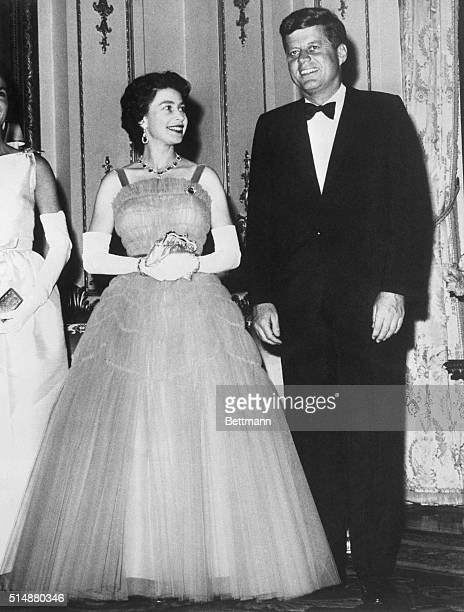 Queen Elizabeth smiles at President John F. Kennedy during a state dinner at Buckingham Palace.
