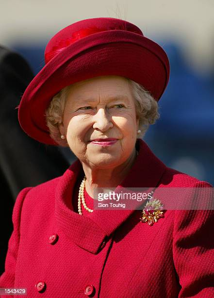 Queen Elizabeth smiles May 18 2002 after presenting a trophy for the 'best turned out trooper' to a Household Cavalry soldier at The Royal Windsor...