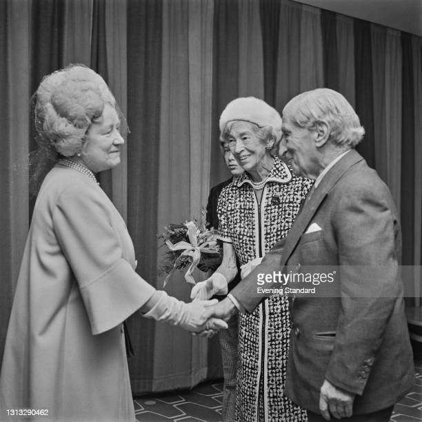 Queen Elizabeth the Queen Mother meets German-born philanthropist Sir Robert Mayer and his wife, Lady Dorothy Moulton Mayer, at the Robert Mayer...