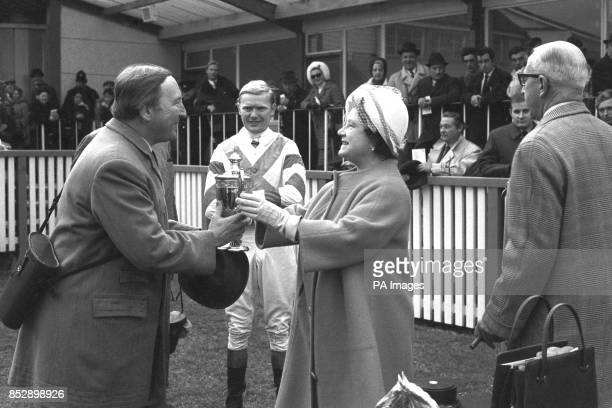 Queen Elizabeth the Queen Mother presents a trophy to AJ Chambers after his horse Gay Trip had won the Mackeson Gold Cup Handicap Steeplechase at...