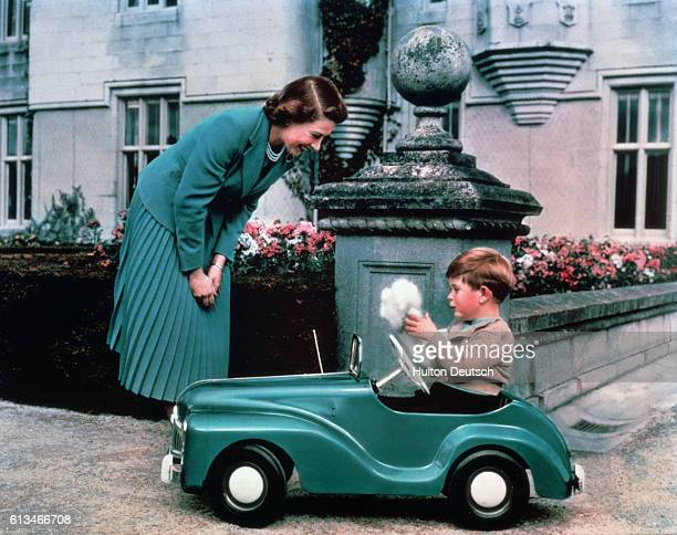 Queen Elizabeth watches her son Prince Charles driving in a toy car on the grounds of Balmoral Castle