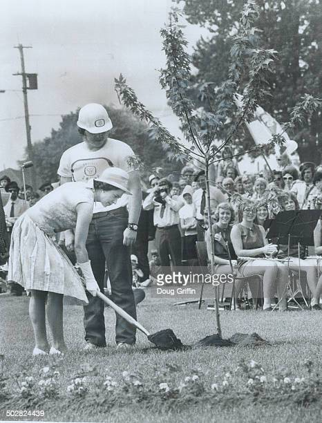 Queen Elizabeth wields a silverplated shovel as she plants a silver maple tree in Ganaraska Conservation area at Cobourg today in commemoration of...