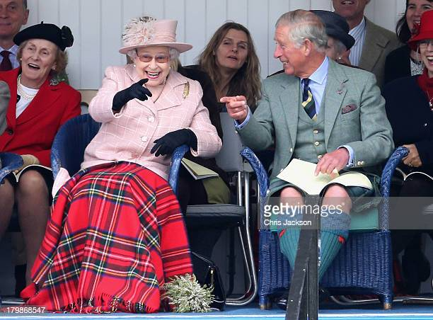 Queen Ellizabeth II and Prince Charles Prince of Wales laugh as they watch the sack race during the annual Braemer Highland Games at The Princess...