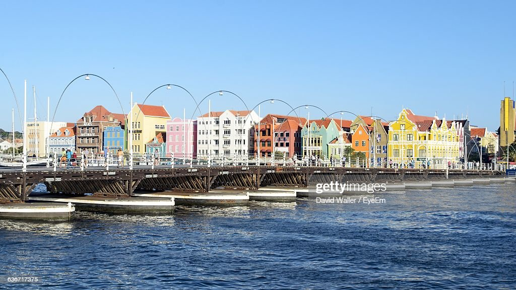 Queen Emma Pontoon Bridge Over Sea By Cityscape Against Sky : Stock Photo
