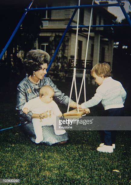 Queen Frederica of Greece with a baby and a small child by a swing, 1981.