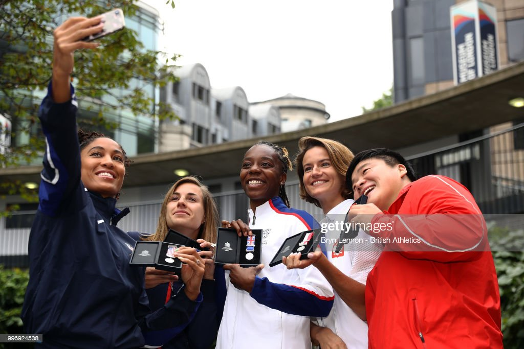 Queen Harrison of the USA takes a selfie with Ninon Guillon-Romarin of France, Lorraine Ugen of Great Britain, Anna Jagaciak-Michalska of Poland and Gong Lijao of China pose for photos at the Athletics World Cup Captains Medal Presentation on July 12, 2018 in London, England. The Athletics World takes place in the London Stadium on the 14th and 15th July.