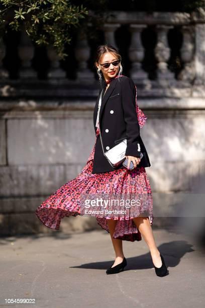 Queen Horsfall wears a black blazer jacket a red pleated dress a silver bag outside Balmain during Paris Fashion Week Womenswear Spring/Summer 2019...