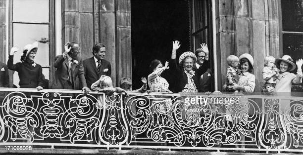 Queen Juliana of the Netherlands and members of the Dutch royal family wave from the balcony of the Lange Voorhout Palace in The Hague, during...