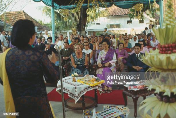 Queen Juliana of the Netherlands pictured seated wearing sunglasses in centre as she listens to a speaker during a Dutch royal visit to Jakarta,...