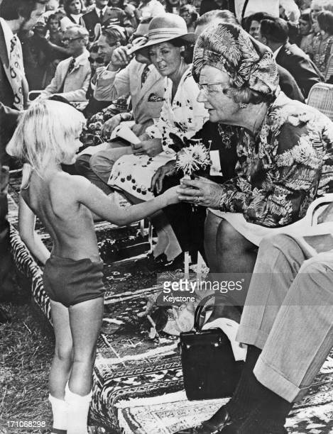 Queen Juliana of the Netherlands recieves a flower from a young boy during celebrations of the Queen's silver jubilee at Tilburg, Netherlands, 6th...