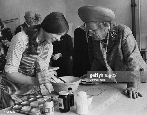 Queen Juliana of the Netherlands watches schoolgirl Susan Oates making cakes in a domestic science class during a visit to Pimlico School, London,...