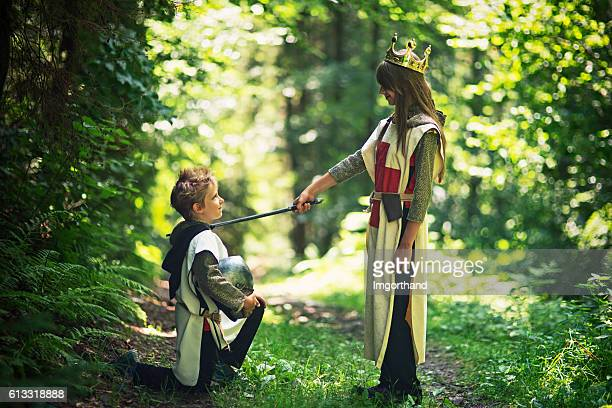queen knighting her loyal knight in forest - medieval queen crown stock pictures, royalty-free photos & images