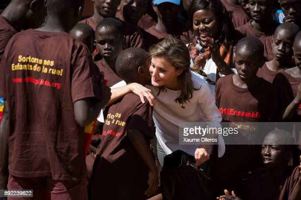 Queen Letizia of Spain hugs a child after receiving a gift as she visits Village Pilote initiative for kids of the streets on December 14 2017 in...