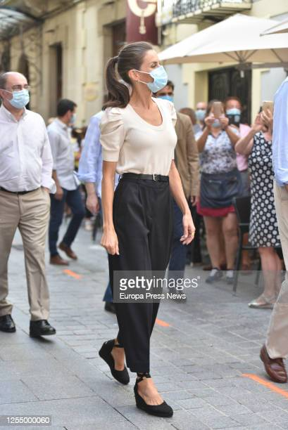 Queen Letizia of Spain is seen greeting the neighbours during her walk through the historic centre of the Pyrenean city of Jaca minutes before...