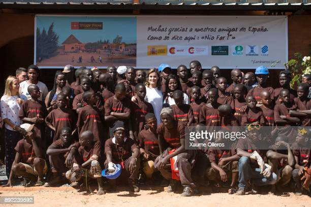 Queen Letizia of Spain poses with students as she visits Village Pilote initiative for kids of the streets on December 14 2017 in Dakar Senegal Queen...