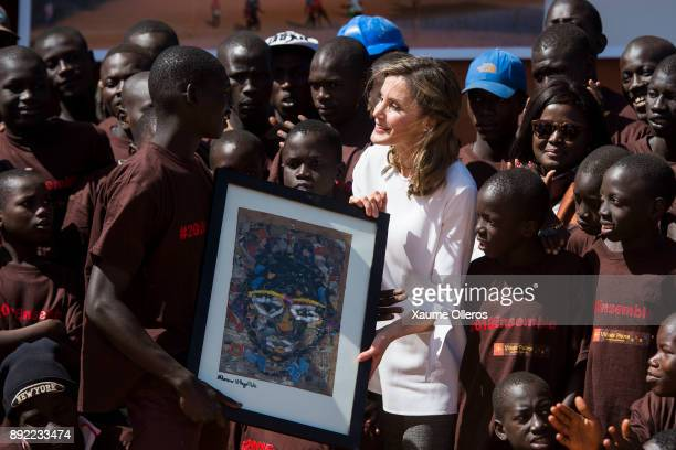 Queen Letizia of Spain receives a gift as she visits Village Pilote initiative for kids of the streets on December 14, 2017 in Dakar, Senegal. Queen...