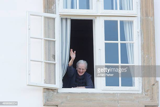 Queen Margarethe II of Denmark waves from the window of Fredensborg Palace during the traditional morning greeting, on her 75th Birthday, on April...
