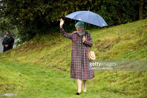 Queen Margrethe II of Denmark waves to wellwishers as she walks on the grounds of the former Danish Danevirke fortification in Dannewerk northern...