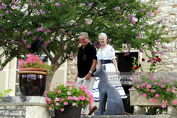 Queen Margrethe II of Dnemark and her husband Prince Henrik stroll in their garden before meeting journalists 11 August 2005 in the castle of Caix...