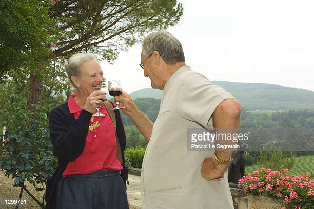 Queen Margrethe of Denmark and her husband Prince Henrik toast each other with wine on the grounds of their Castle of Caix August 8 2002 in the...
