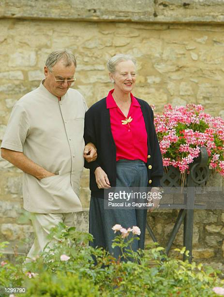 Queen Margrethe of Denmark and Prince Henrik walk on the grounds of their Castle of Caix August 8 2002 in the village of Caix in southwestern France...