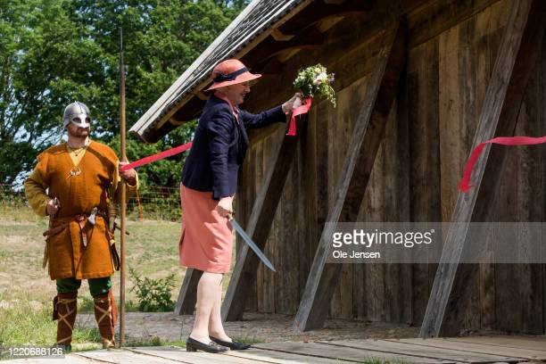 """Queen Margrethe of Denmark cut the red ribbon with a Viking sword during the to the opening ceremony of the world largest Viking Hall at the """"Land of..."""