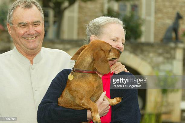 Queen Margrethe of Denmark holds her dog Celimen as her husband Prince Henrik stands beside her on the grounds of their Castle of Caix August 8 2002...