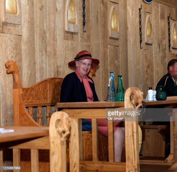 """Queen Margrethe of Denmark is seated at the Kings table during the inauguration of the great Viking Hall at the """"Land of Legends"""" open air museum on..."""
