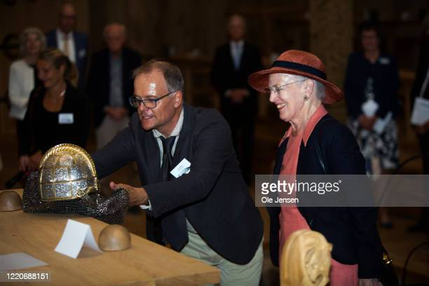 """Queen Margrethe of Denmark is shown a Viking warriors helmet during the inauguration of the great Viking Hall at the """"Land of Legends"""" at Lejre open..."""
