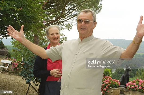 Queen Margrethe of Denmark stands behind her husband Prince Henrik as he gestures on the grounds of their Castle of Caix August 8 2002 in the village...