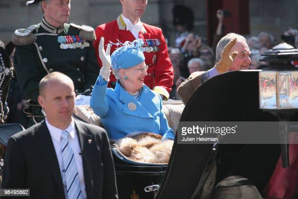 Queen Margrethe of Denmark waves to wellwishers from a carriage next to Prince Consort Henrik during celebrations marking her 70th birthday on April...