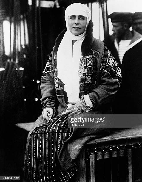 Queen Marie of Romania sits on a case while a sailor stands behind her. Marie was Queen of Romania with husband King Ferdinand from 1914 to 1927.